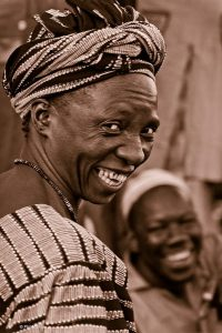 Photograph of an African woman laughing mischievously, and a man laughing in the background. Scenes like this remind one of joking relationships.
