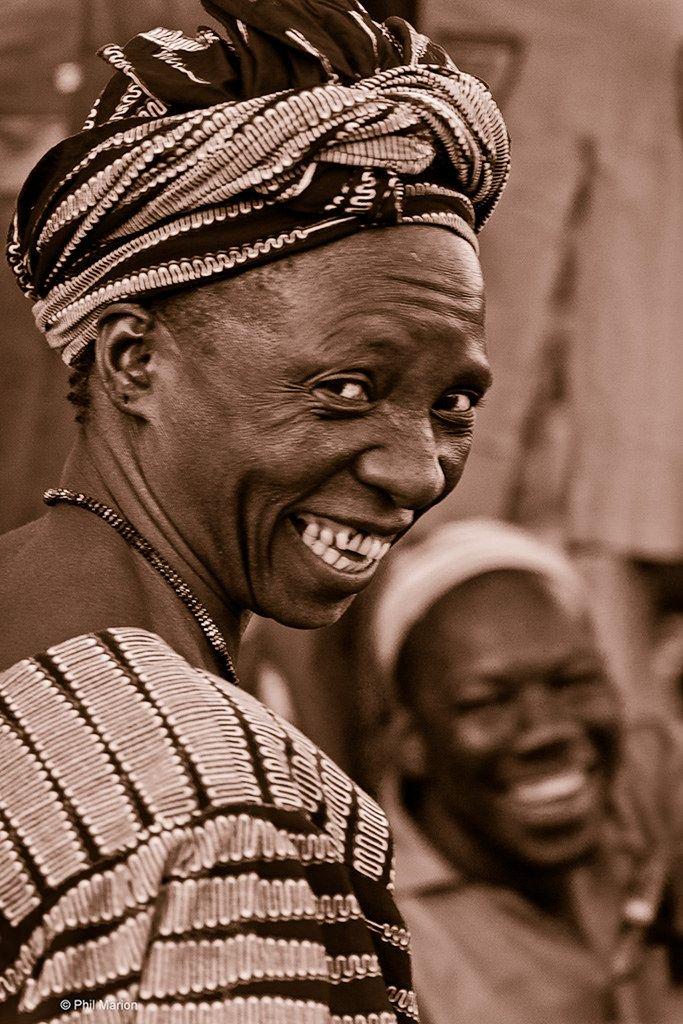 Photographie d'une femme africaine en train de rire malicieusement, et un homme riant en arrière plan. Ce genre de scène est commun dans les parentés à plaisanterie.