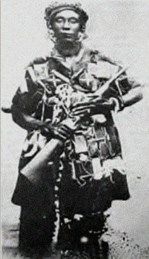 Queen mother Yaa Asantewa in ceremonial war dress, carrying a rifle