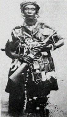 Le reine mère des Ashanti, Yaa Asantewa portant la tenue traditionnelle de guerre ainsi qu'un fusil.