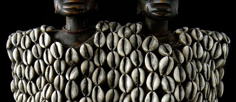 Cowrie shells adorn two wooden Yoruba Ibeji dolls.