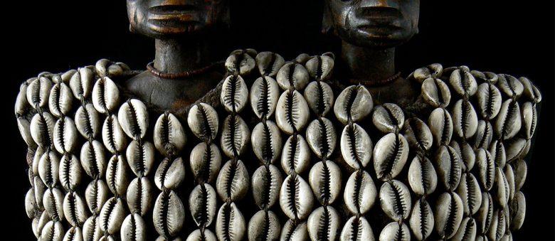 Des cauris ornent deux poupées Ibeji en bois des Yorubas.