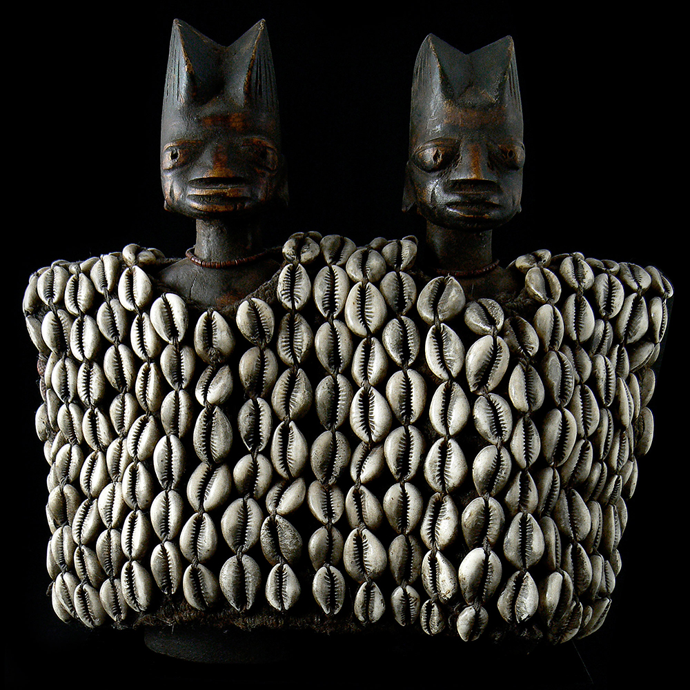 The cowrie shell monetary and symbolic value cultures of west africa cowrie shells adorn two wooden yoruba ibeji dolls publicscrutiny Image collections