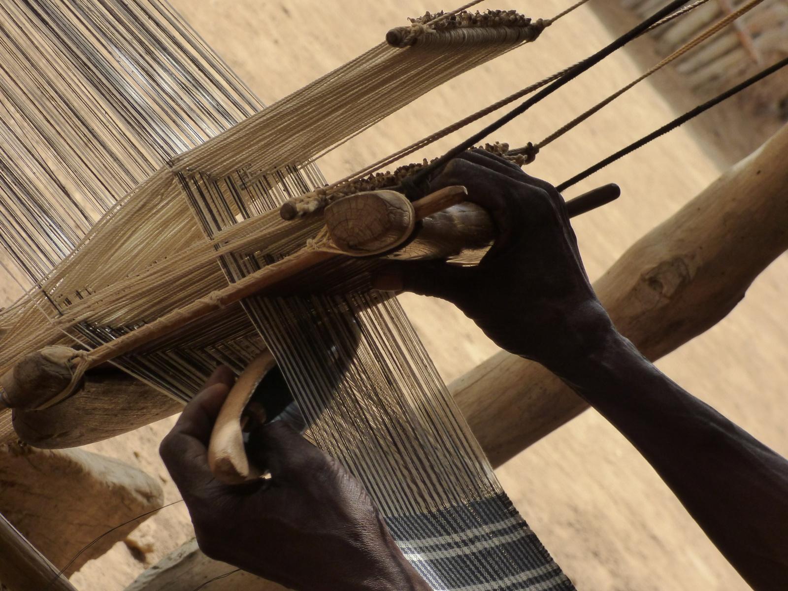 Gros plan sur les mains d'un tisserand Dioula, passant la navette à travers la trame du métier à tisser.