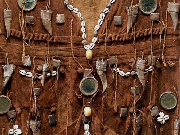 Mudcloth hunter's shirt: rust-toned traditional bògòlanfini (bogolan) textile with attached symbolic amulets.