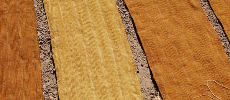 Photographir de bandes de cotton teintes avec de la terre qui sèchent sous le soleil. Une fois cousus et peints, ceux ci deviendront du bògòlanfini (ou bogolan).