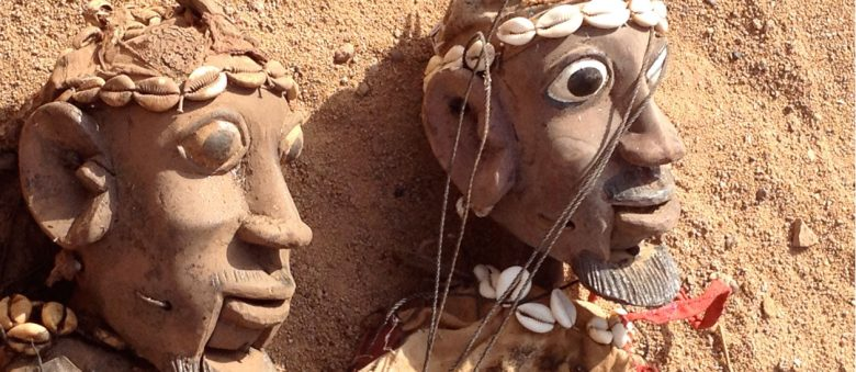 The heads of two West African puppets articulated at the mouth and adorned with cowrie shells, awaiting the puppeteer.