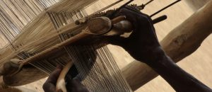 Close up of the hands of a Dyula weaver, threading the shuttle though the loom.
