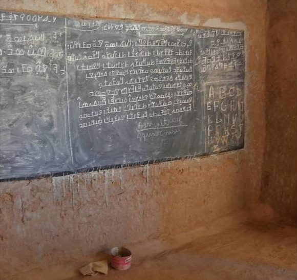 Photograph of a blackboard in a modest schoolhouse in Mali, Africa. On it is a text in N'Ko, used to teach students to read.