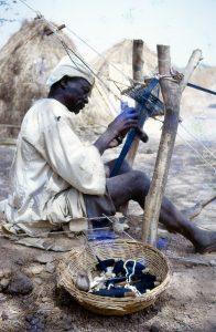 Un tisserand du Nigéria, portant des habits traditionels, assis sur le sol, tissant avec un métier rustique.