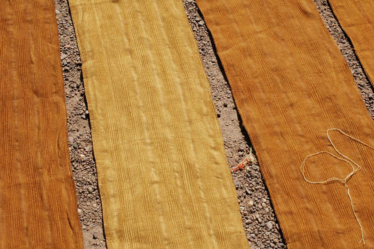 Photograph of strips of mud dyed cloth drying in the sun, that will become bògòlanfini (mudcloth or bogolan)