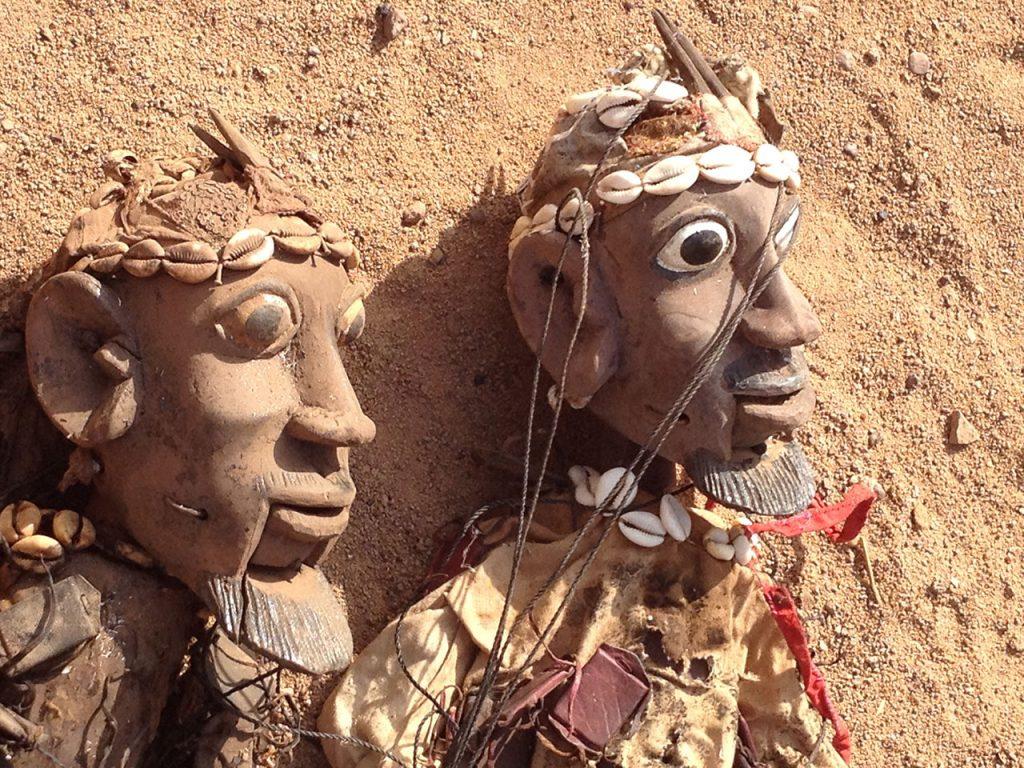 Têtes de deux marionnettes ouest africaines, articulées à la bouche et ornées de cauris, qui attendent le marionnettiste.