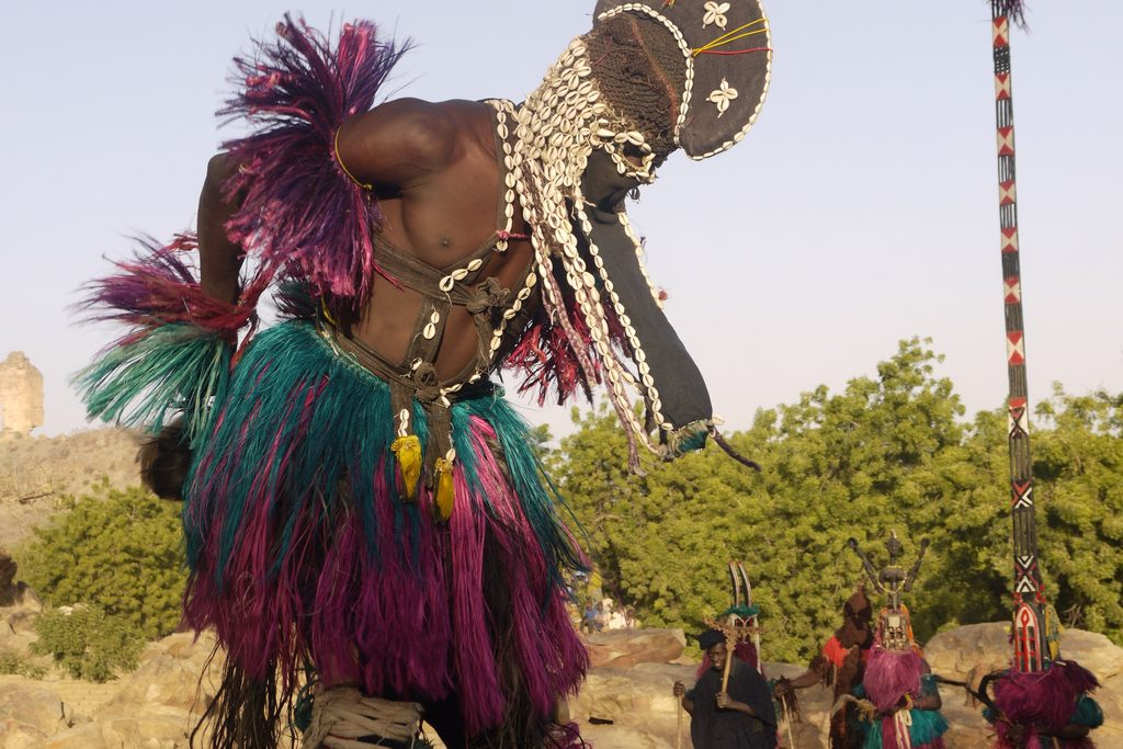 Tene Tana - Dogon stilt dancer with Sirige mask in background