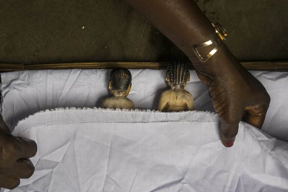 """""""Benin's Living Dead"""", documenting the Fon's twin effigies. In this photography, someone is putting the statues to bed."""