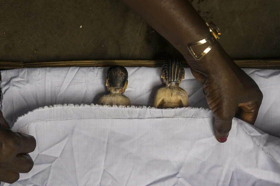 """""""Les morts-vivants du Bénin"""", une série qui documente les effigies des jumeaux Fons. Dans cette photographie, les statuettes sont mises au lit."""