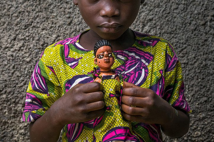 """""""Benin's Living Dead"""", documenting the Fon's twin effigies. In this photography, a boy carries the statue of his twin."""