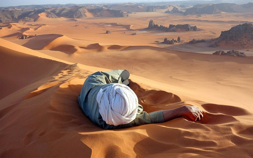 Picture of a Tuareg man laying in the sands at the top of an erg in the Sahara desert.