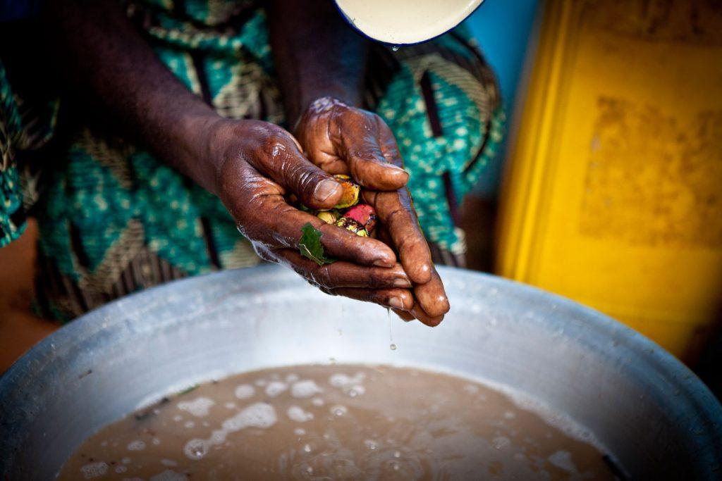 Vodoun devotee cleansing ceremonial kola nuts, Ouidah, Benin