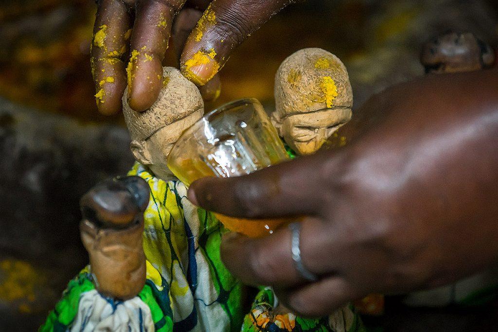 """""""Les morts-vivants du Bénin"""", une série qui documente les effigies des jumeaux Fons. Dans cette photographie, quelqu'un nourrit les statues."""