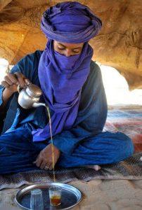 Photo d'un homme touareg servant le thé dans sa tente dans le désert du Sahara.