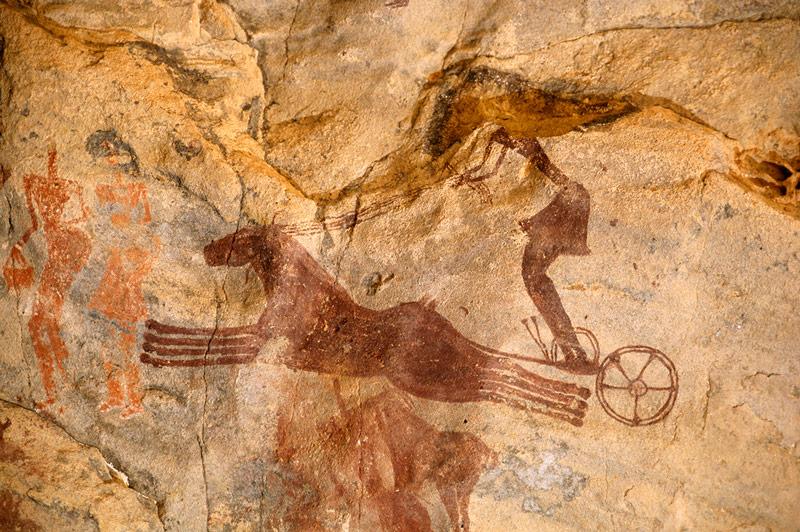 Art rupestre du Tassili n'Ajjer, dans le désert Saharien en Algérie du sud-ouest. Peinture de deux chevaux gallopant vers la gauche qui tirent un char avec un aurige qui porte une jupe et tient quatre rênes.