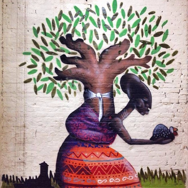 Mural painting of a Yoruba woman wearing a colorful red dress, her arm extended to offer a bird. She carries a baobab tree on her back, as she would a child.