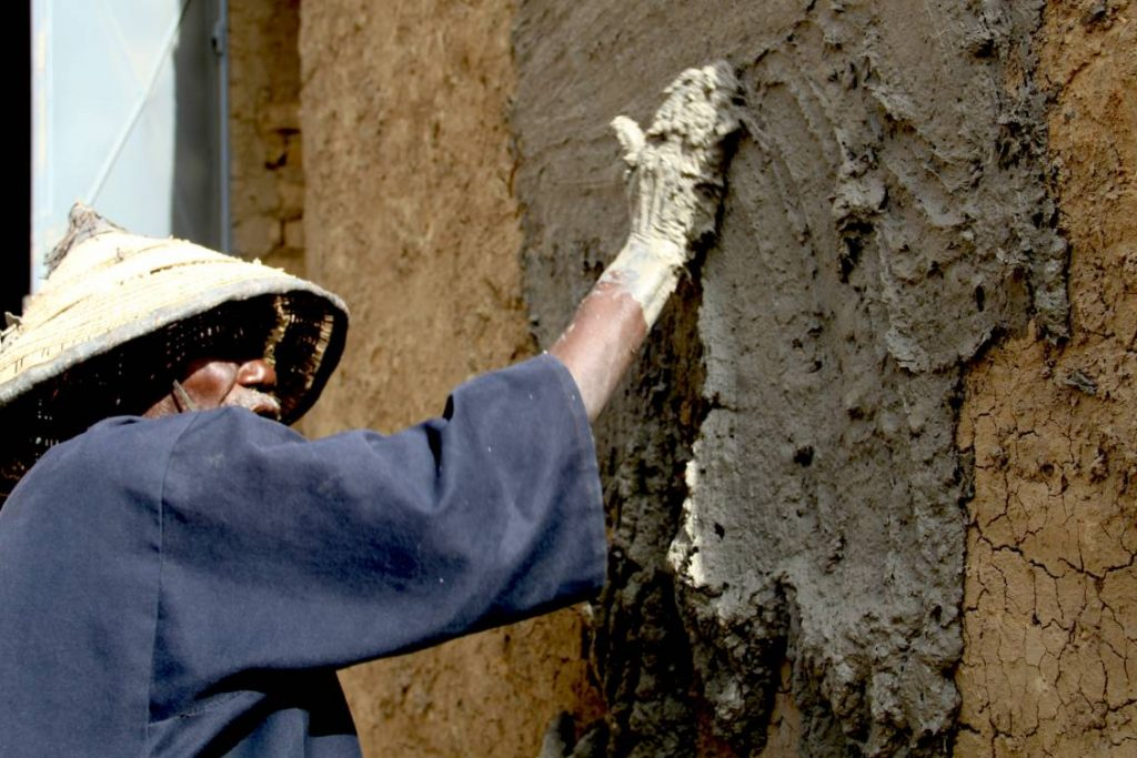 Annual plastering of the Great Mosque of Djenné in Mali. Photography of an old master mason, demonstrating the proper way to plaster.