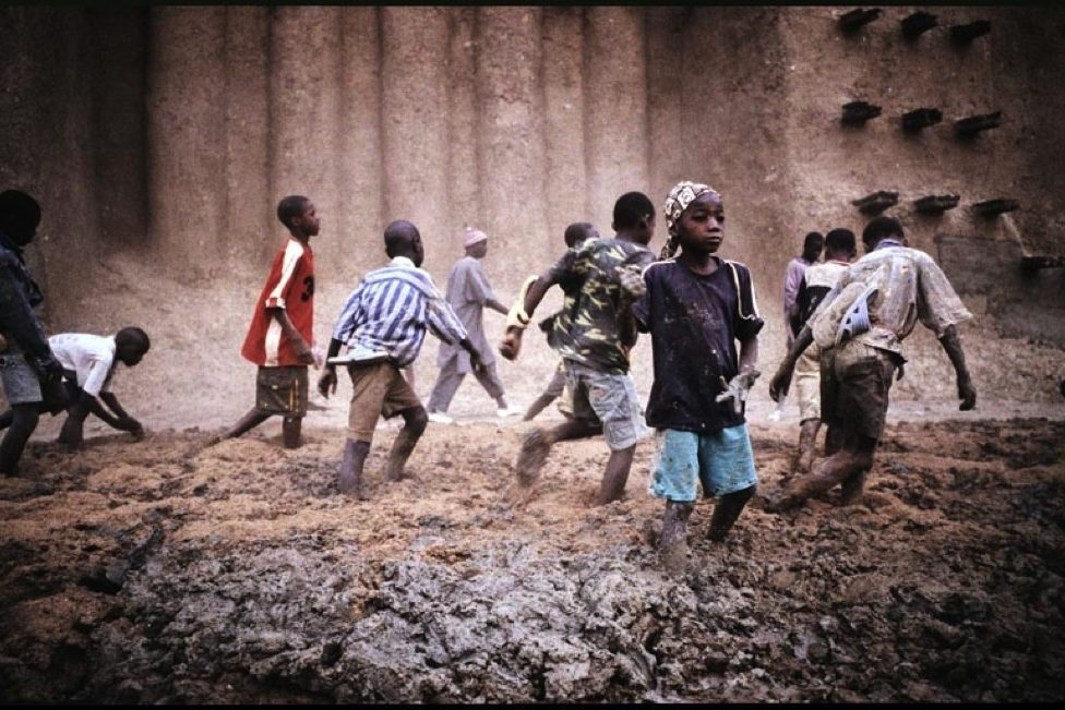 Annual plastering of the Great Mosque of Djenné in Mali. Photography of children playing in the mud while the masons re-plaster the mosque.