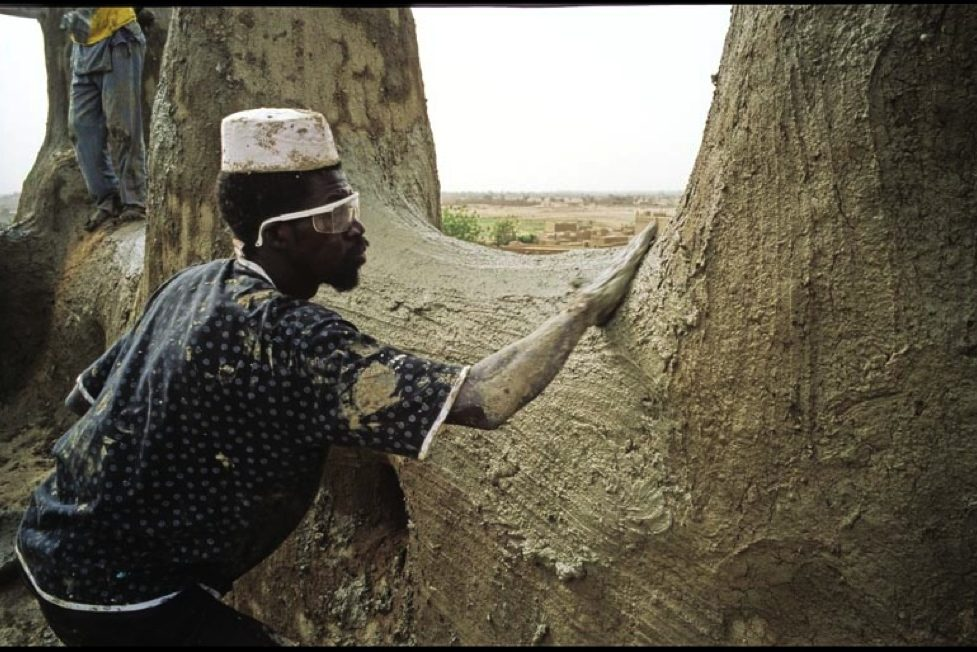 Annual plastering of the Great Mosque of Djenné in Mali. Photography of a master mason spreading plaster on the top of the mosque.
