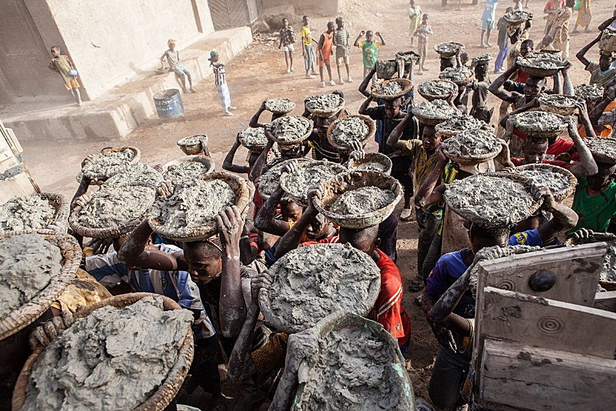Annual plastering of the Great Mosque of Djenné in Mali. Photography of people carrying plaster in baskets on their heads to the masons awaiting at the mosque.