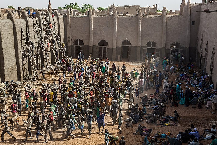 Annual plastering of the Great Mosque of Djenné in Mali. Photography of a crowd, carrying baskets of mud on their heads to the masons awaiting at the mosque, while other people rest in the shade.