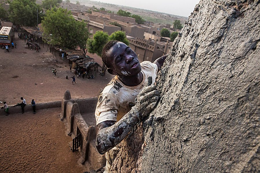 Annual plastering of the Great Mosque of Djenné in Mali. Photography of a mason who climbed very high to replaster a minaret without any safety gear. Far below, other masons are taking a break.