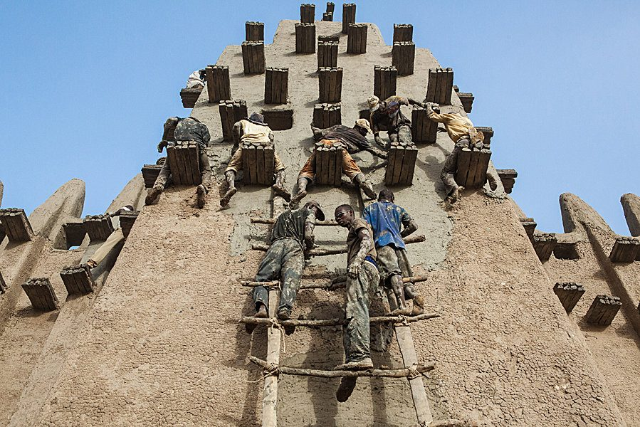 Annual plastering of the Great Mosque of Djenné in Mali. Photography from below of the masons climbing on the permanent scaffolding to replaster a minaret.