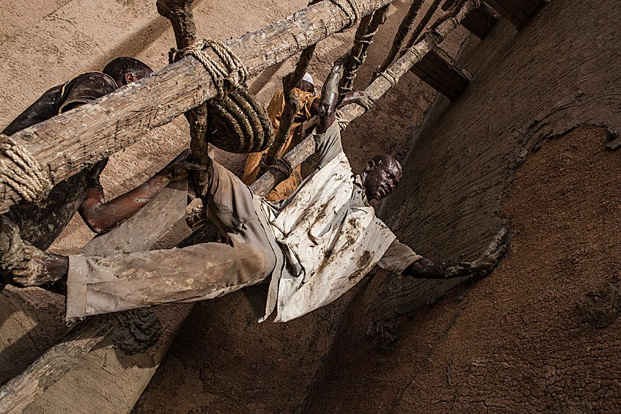 Annual plastering of the Great Mosque of Djenné in Mali. Photography of a master mason clinging to the scaffolding and stretching to reach the wall he is plastering.