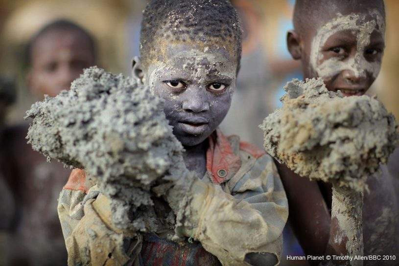 Annual Plastering of the Great Mosque of Djenné in Mali. Photography of children covered in plaster, preparing it for the masons re-plastering the mosque.
