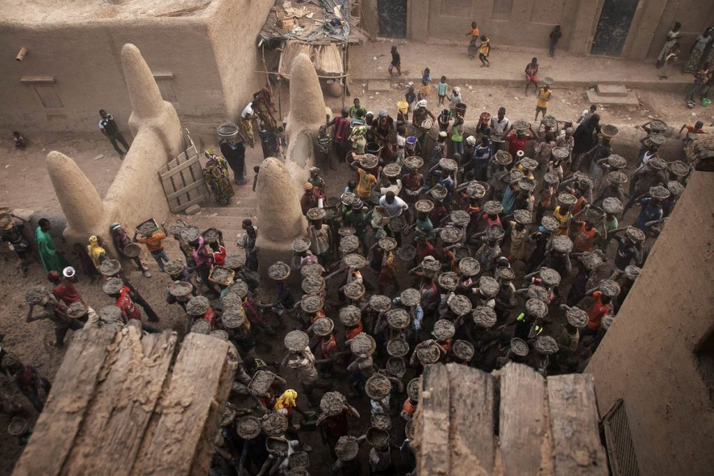 Annual plastering of the Great Mosque of Djenné in Mali. Photography from high above a crowd, each person carrying baskets of mud on their heads to the masons awaiting at the mosque.