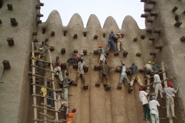 Annual plastering of the Great Mosque of Djenné in Mali. Photography of the maçons of Djenné climbing the high walls of the mosque.