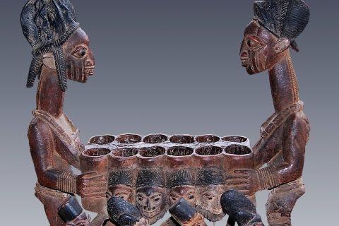 Tablier de mancala royal en bois peint, représentant des personnages humains portant les deux côtés du tablier, avec d'autres personnages dansant à la base. Créé par l'artiste yorouba Olowe d'Ise dans les années 1920.