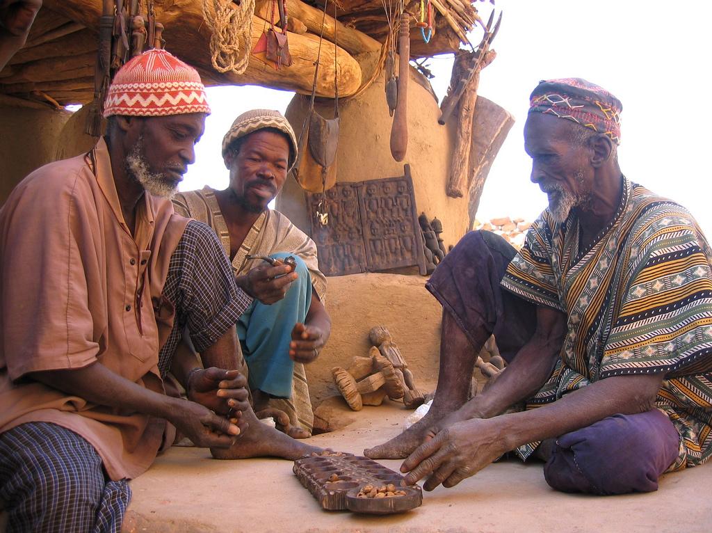 Trois hommes Dogon jouent au mancala à l'ombre du Toguna, ou case à palabre, au Mali, photographie de Staffan Martikainen.