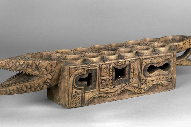 Tablier de mancala orné, en forme de crocodile, créé par le peuple Ekoi du sud-est du Nigéria, fait de bois et d'étain.