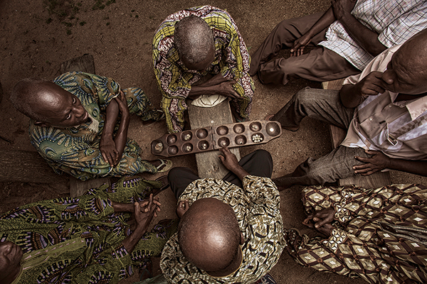 Village elders gathered around in the village square to watch two men playing a game of mancala in Yagba, Kebbi state, Nigeria