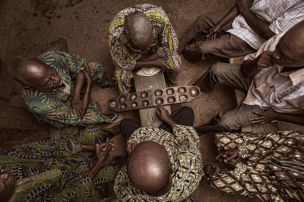 Les anciens du village se rassemblent dans la cour pour regarder deux hommes jouer à un jeu de mancala à Yagba, Etat de Kebbi, Nigeria