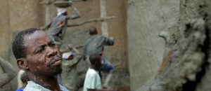 Crépissage annuel de la Grande Mosquée de Djenné au Mali. Photographie d'un maître maçon qui enduit les murs de plâtre pendant que derrière lui, d'autres maçons grimpent l'échaffaudage.