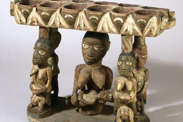 Tablier de mancala en bois créé par les Yoroubas du Nigéria, qui représente des cavaliers et une femme portant un enfant. Le tablier est posé sur les têtes des personnages. Créé par les Yoroubas du Nigéria.