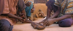Three Dogon men playing the mancala game in the shade of the toguna or palaver awning, Mali, by Staffan Martikainen.