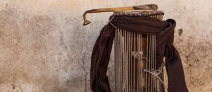 Photograph of a West African talking drum, in the shape of an hourglass with tension strings surrounding its sides and a scarf tied loosely around the top. On top of the drumhead lies the curved percussion stick used to beat the drum.