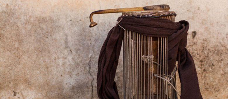 Photographie d'un tambour parleur ouest-africain, en forme de sablier avec des cordes de tension autour de ses côtés et une écharpe lacée autour. Au dessus de la peau du tambour est posée la baguette courbée avec laquelle on frappe le tambour.