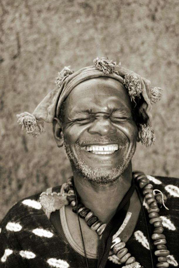 Sepia photography of a Mande clown in the Segou region, laughing. He is dressed in traditional rags.