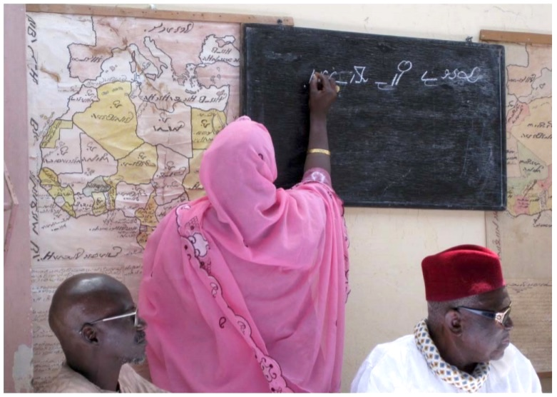 Photographie d'une femme en train d'écrire le wolof avec l'alphabet Garay sur une ardoise. Sur le mur sont affichées des cartes géographiques en Garay.