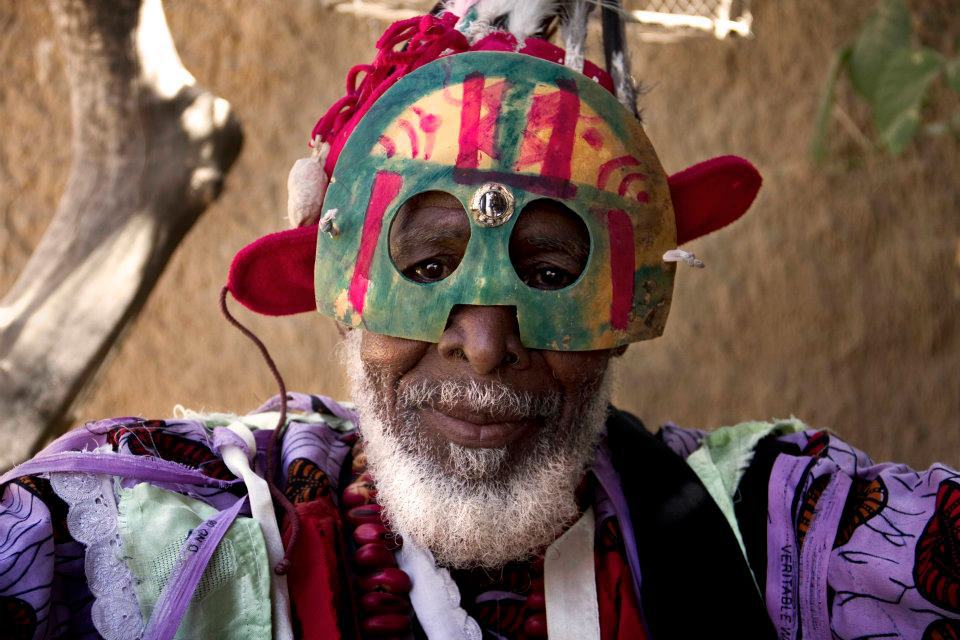Photography of the chief korèduga of Mimana in Mali. The clown or buffoon is wearing strips of torn cloth and a colorful monkey mask.